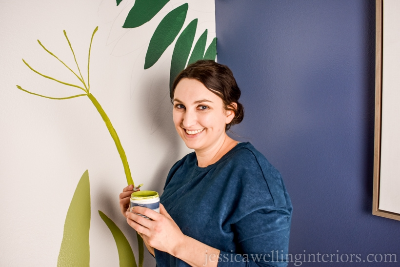 woman painting a mural accent wall in a small powder room with leaves and flowers