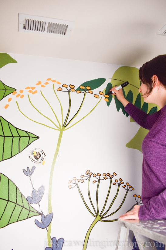 woman standing on ladder, outlining botanical mural painting with a black paint pen