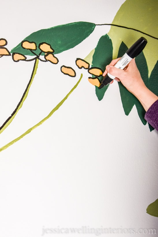 close-up of hand outlining yellow flowers with a black paint pen on a hand-painted mural in a small powder room