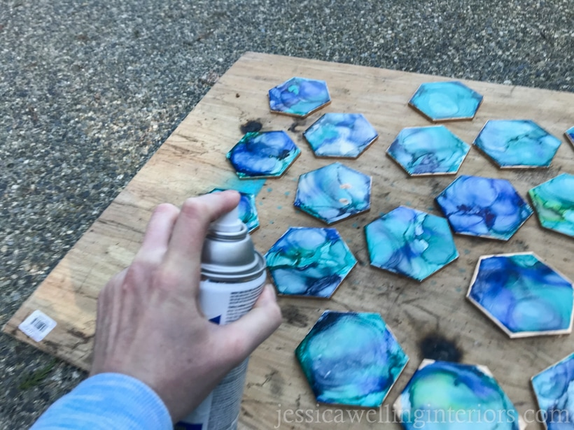 hand spray-painting clear coat on DIY tile coasters to make them waterproof