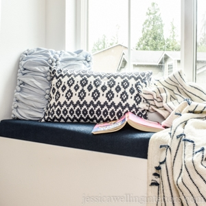 navy blue upholstered window seat cushion with throw pillows, a blanket, and a children's book