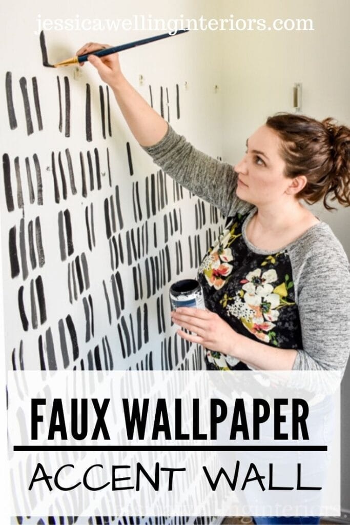Faux Wallpaper Accent Wall: woman painting black brush strokes on a white wall to create a modern patterned accent wall