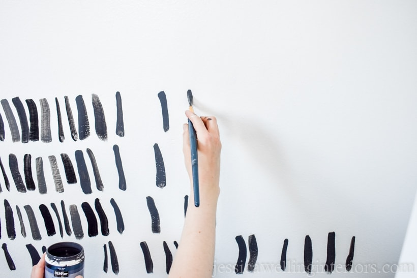hand painting a grey brush strokes on a diy accent wall