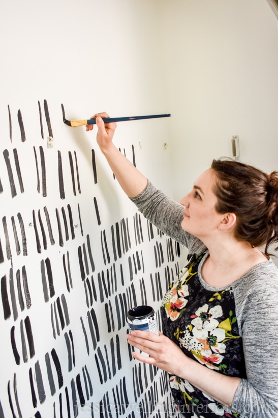 woman creating a painted accent wall with a modern black and white pattern