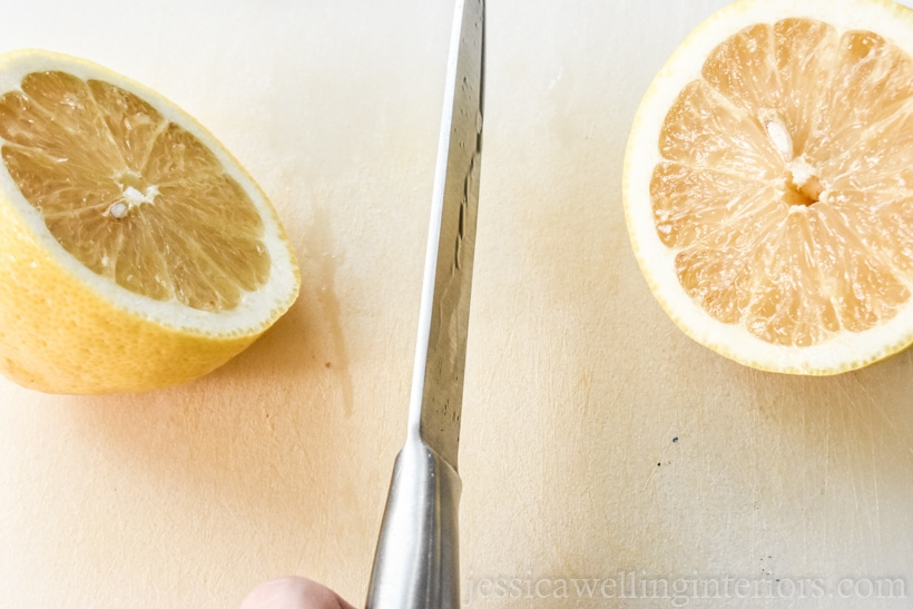 knife cutting a lemon in half to prep it for printing tea towels