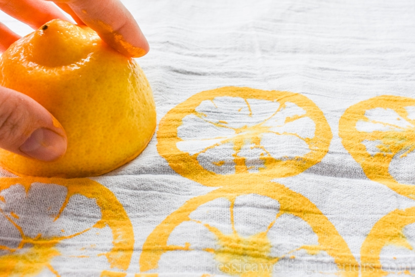 hand using a lemon half to print a pattern on a flour sack kitchen towel