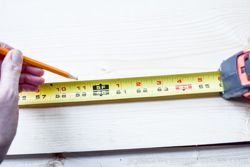 measuring tape and hand with pencil marking board to make DIY vertical garden planter