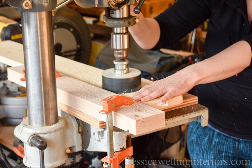 close-up of woman using drill press to cut hole in indoor vertical garden shelf to hold pots with faux hanging plants