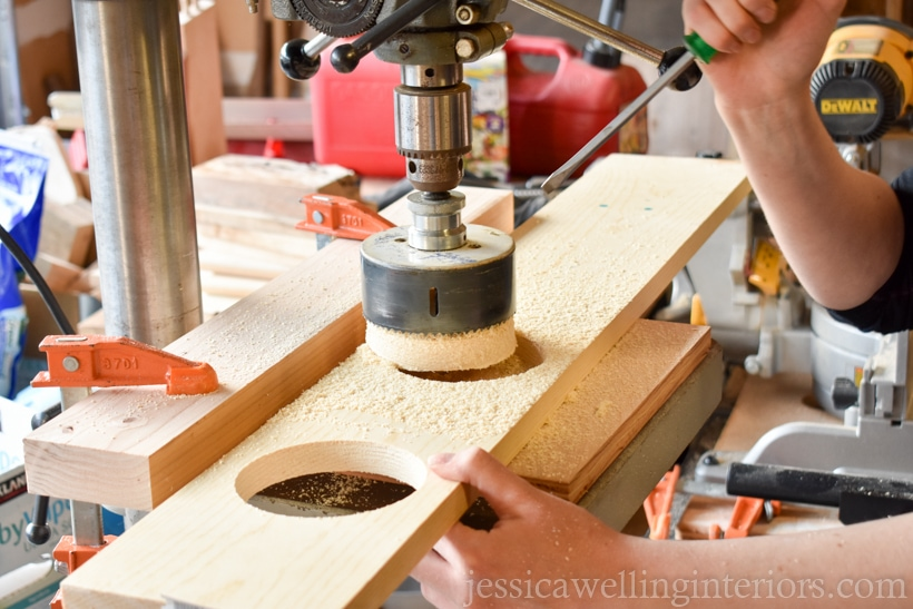 hands using screw driver to remove wood cutout from hole saw on a drill press to make a vertical garden