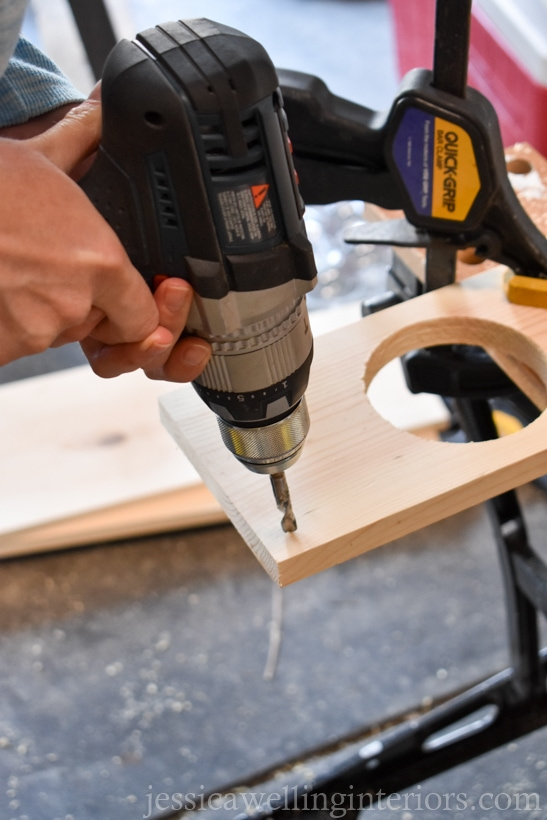 close-up of handing using drill to drill holes in a wood vertical wall garden shelf