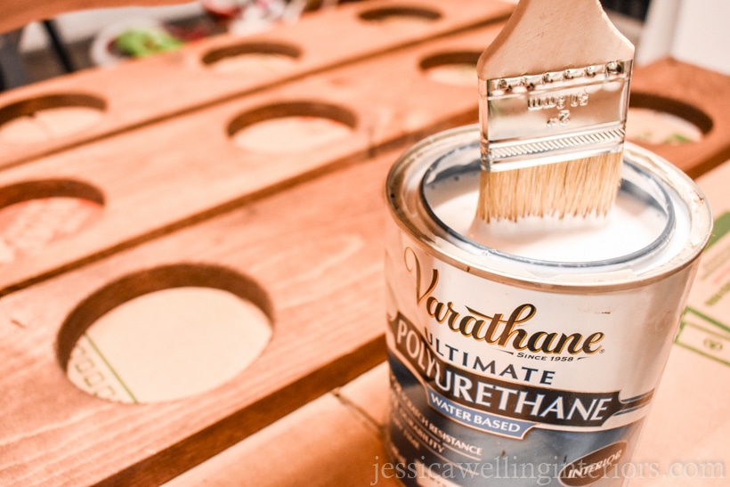 close-up of paintbrush being dipped into open can of Varathane polyurethane clear coat sealer with vertical garden shelves in the background