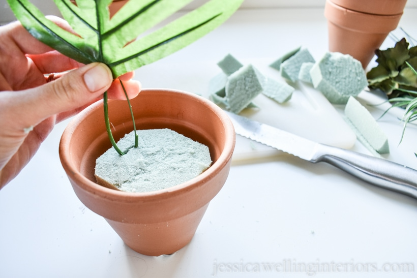 hand placing faux plant stem into floral foam in a terra cotta pot