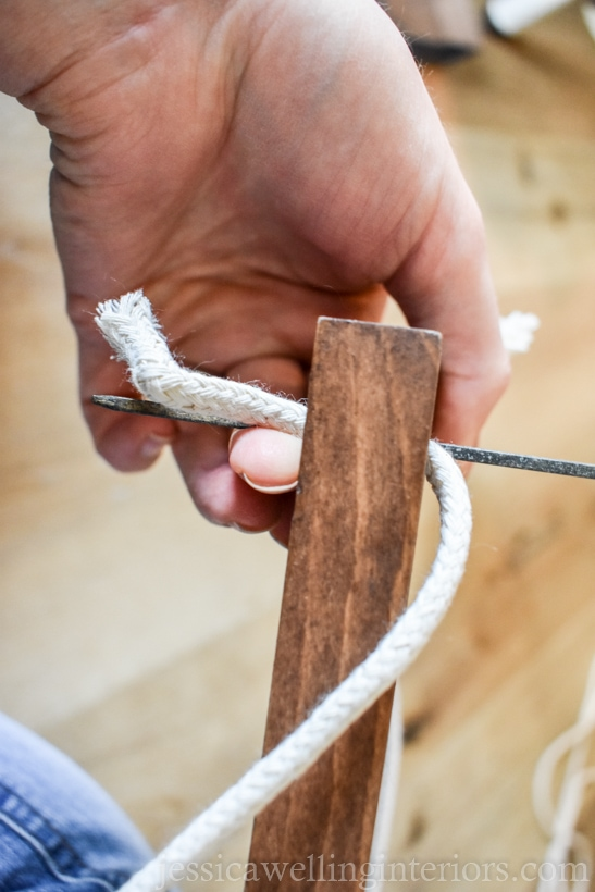 close-up of hand using a skewer to poke rope through a hole drilled in a vertical garden shelf