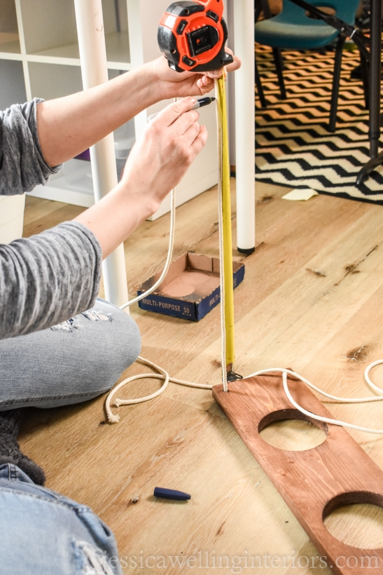 woman using measuring tape to mark the correct length of rope to hang an indoor wall garden with faux plants