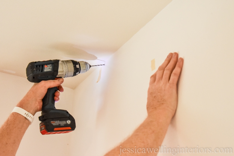 hand holding a drill, drilling into upper corner of a white wall to hang an artificial vertical garden