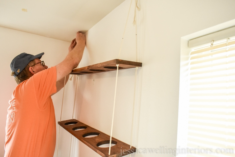 man hanging DIY vertical garden on hooks on the wall