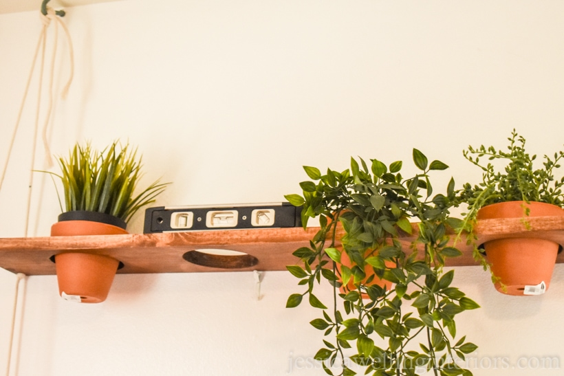wood vertical garden shelf being measured with a level