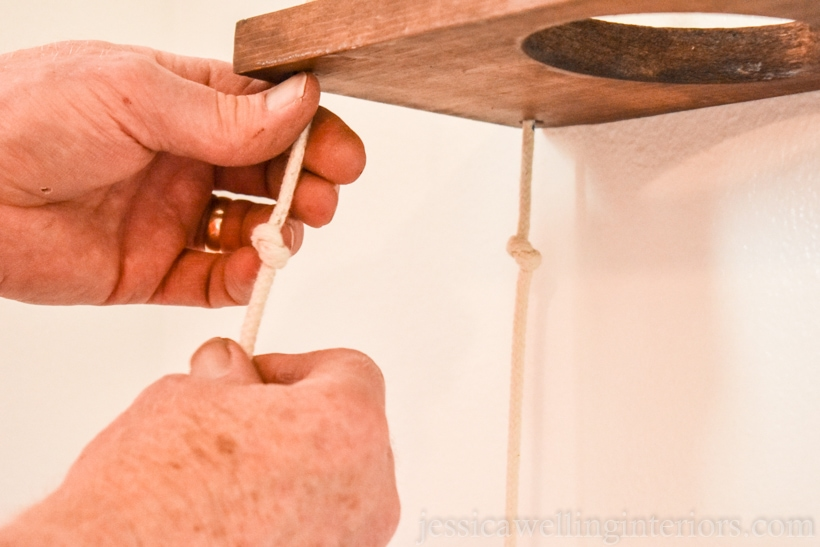 close-up of hands adjusting knots in the ropes suspending wood vertical garden shelves