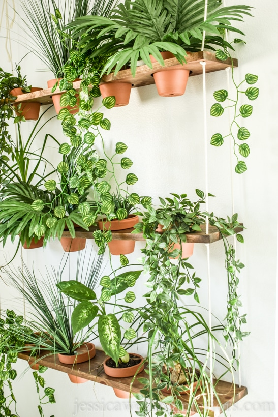 side angle view of DIY vertical garden with terra cotta pots and indoor hanging plants