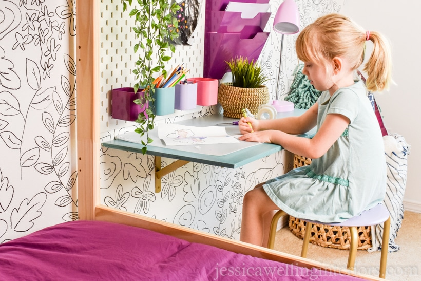 child working at a desk with artificial plants in the foreground and on the desk