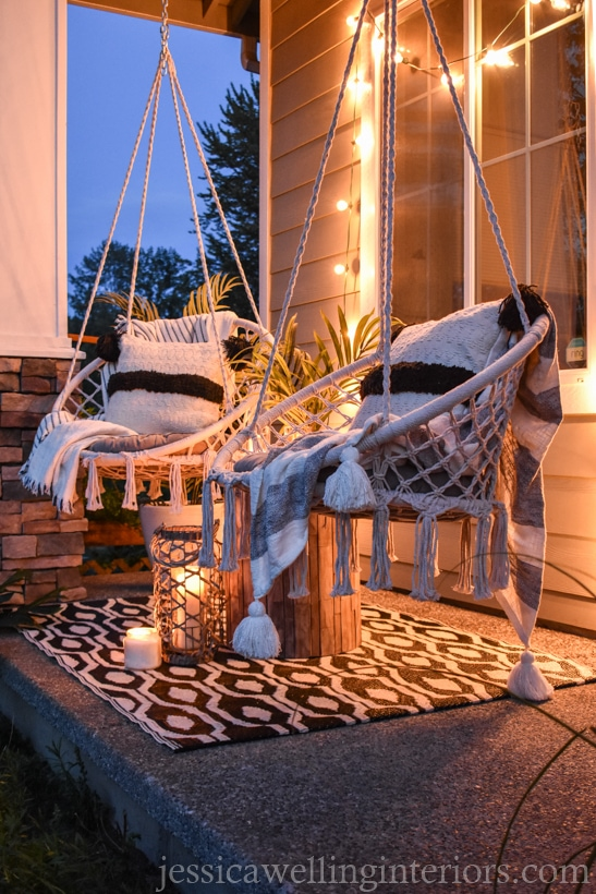 Boho porch at dusk with two macrame swing chairs, glowing string lights, an outdoor rug, outdoor pillows, and blankets