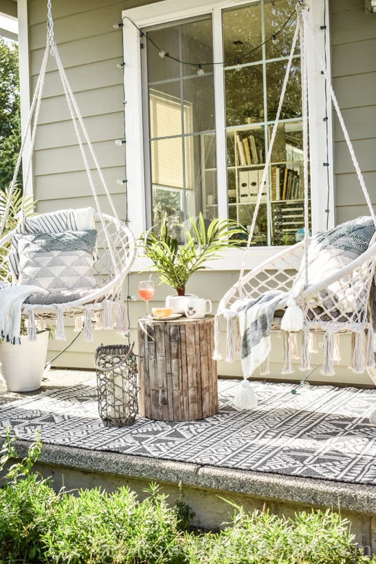 2 Boho porch swings with sring lights, an outdoor rug, and an end table