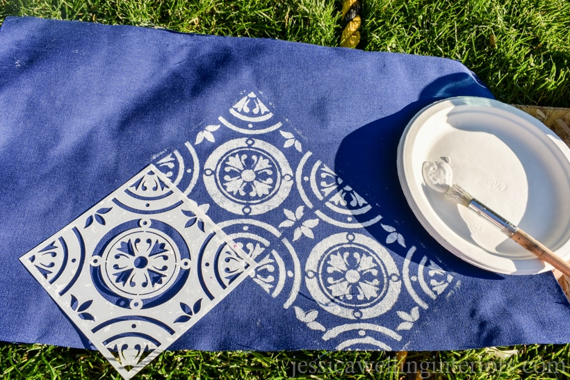 Outdoor fabric being stenciled with a Moroccan tile pattern and white craft paint