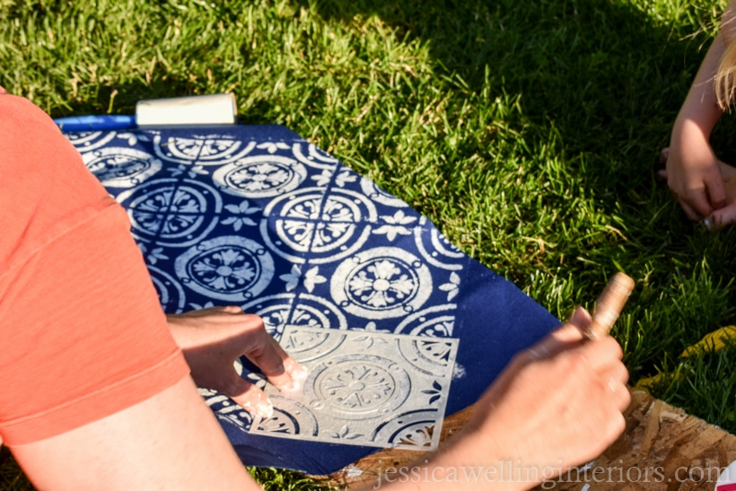 woman using a stencil brush to apply paint to blue outdoor fabric for DIY outdoor pillows