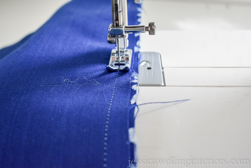 close-up of blue outdoor pillow seams being reinforced using a sewing machine