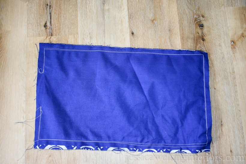 dark blue pillow cover sewed together, but still inside-out laying on the floor