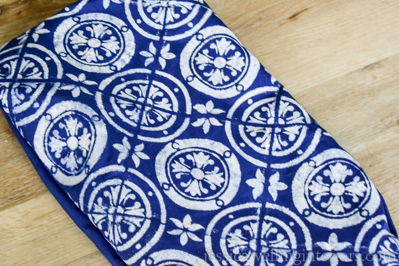 case for a dark blue outdoor pillow with a white stenciled tile pattern, ready to be stuffed