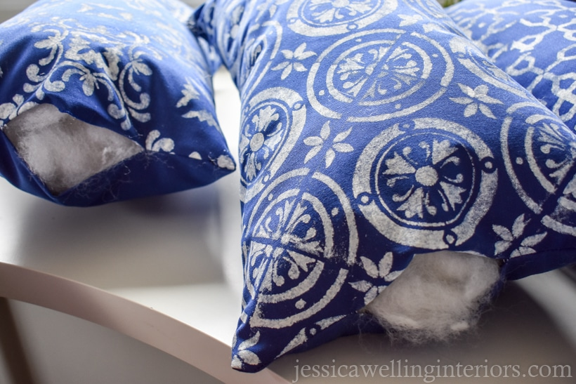 three blue outdoor lumbar pillows stuffed, and ready to be sewed closed