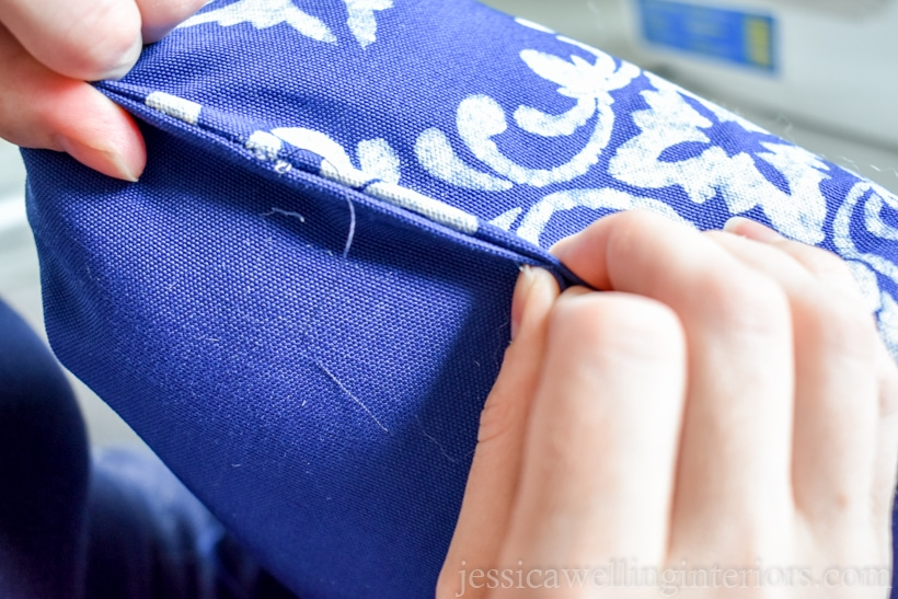 close up of hands holding the opening of an outdoor throw pillow closed to pin it before sewing