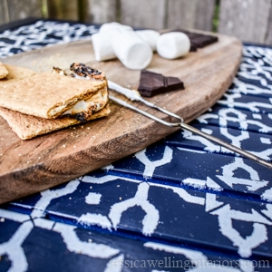 outdoor table stenciled with white paint and s'mores on a wood cutting board