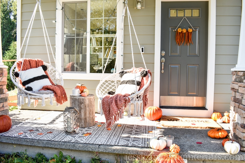 small front porch decorated for Fall- modern macrame swing chairs with cozy throw pillows and blankets, pumpkins, string lights, and a Boho wall hanging on the front door