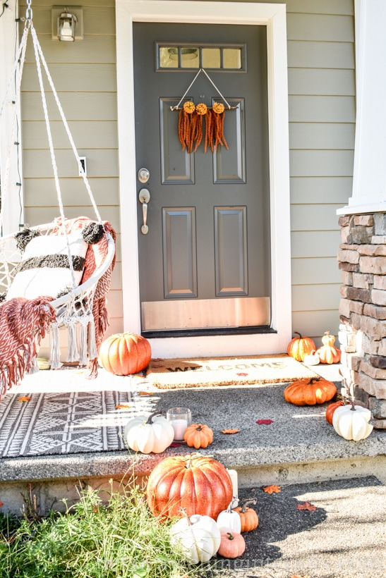 front door and porch decorated for Fall, with a modern Boho wreath and pumpkins