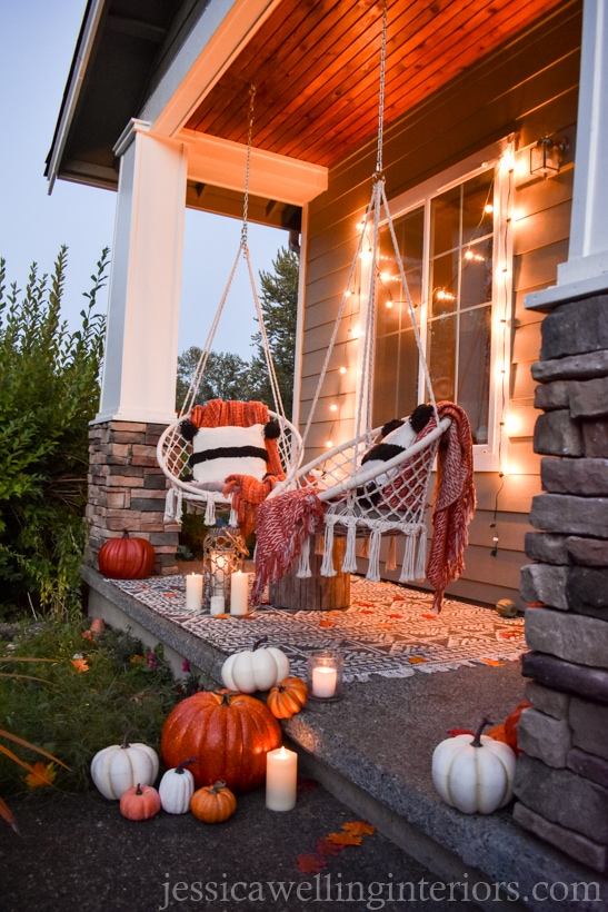 low-light photo of Fall porch decor with modern Boho swings, pumpkins, throw pillows, and blankets, candles, and string lights