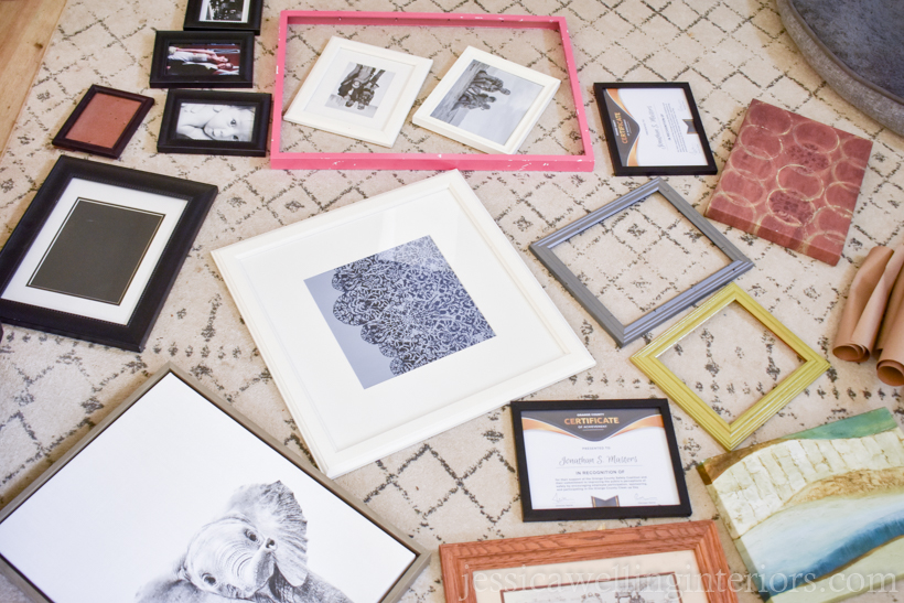 a variety of old picture frames laid out on the floor