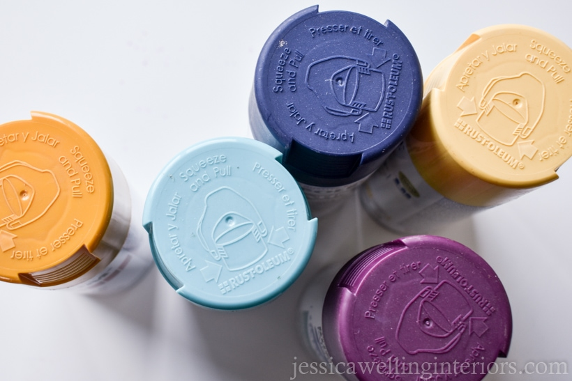 top view of five cans of spray paint in mustard yellow, purple, navy blue, teal, and light yellow