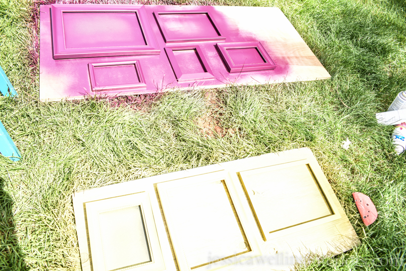 piece of plywood laying on grass, with several picture frames being spray painted purple and yellow