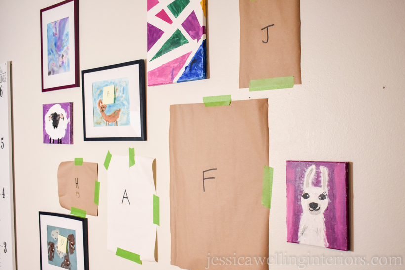 partially completed kids art display wall with some templates and some pieces of art already mounted to the wall