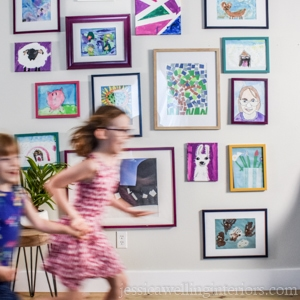 kids art display gallery wall with two kids running