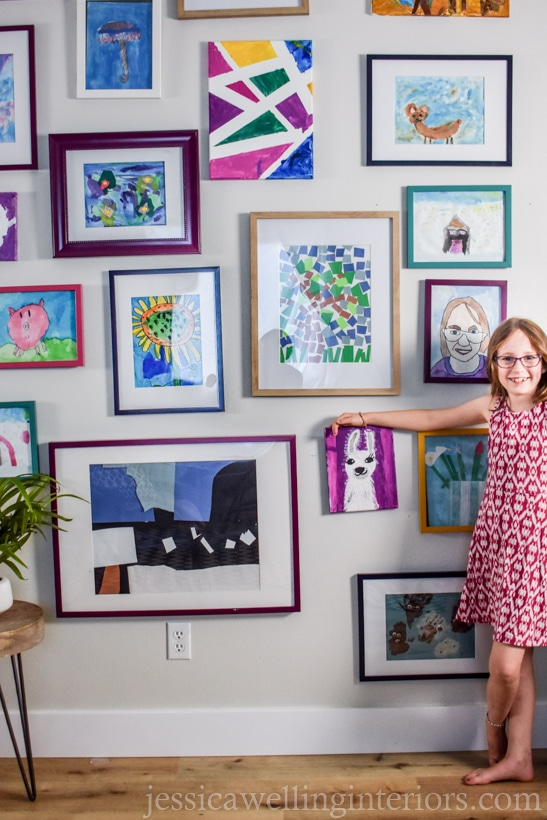 finished kids art display wall with a little girl pointing to a llama painting