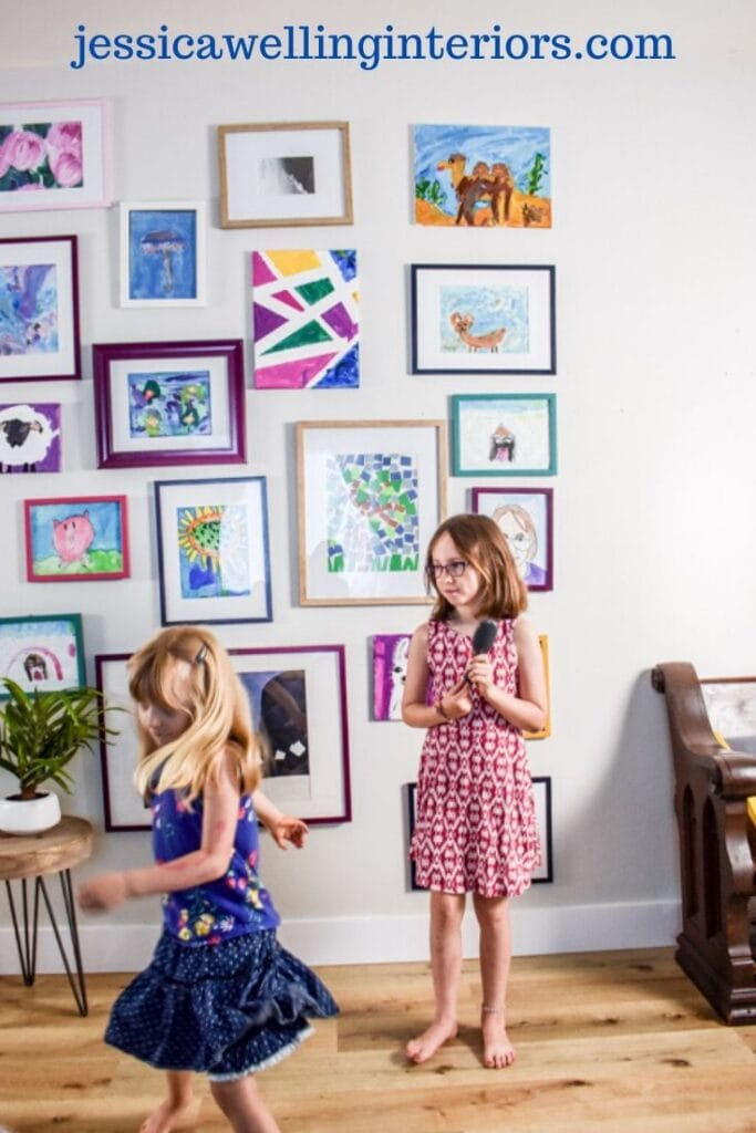 kids' art gallery wall with two little girls singing and dancing in front of it