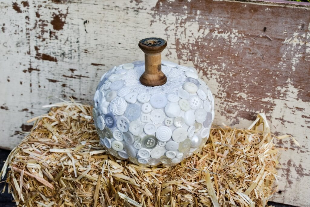 close-up of white pumpkin decor, with buttons sitting on a hay bale