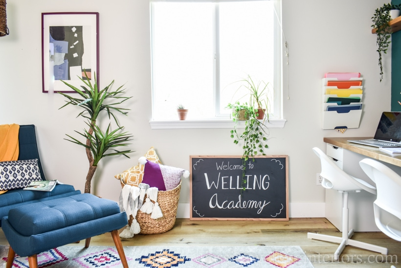 "finished homeschool room with a chalkboard sign that reads, ""Welcome to Welling Academy"", a distance learning desk, rug, and reading nook"