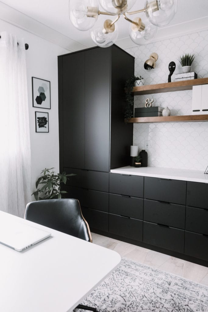 Ikea home office with black cabinetry, floating shelves, and a mermaid scale  tile wall