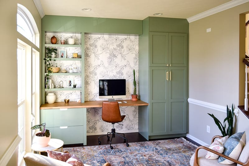 light green Ikea-hacked desk wall with built-in storage, bookshelf, and file cabinet.