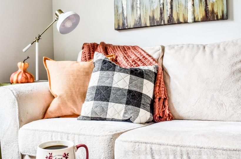 Fall throw pillows and an orange throw blanket on a sofa