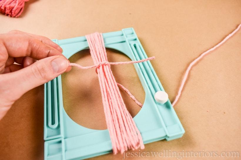 hand tying a yarn tassel